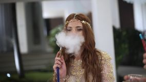 Man and woman at the party having fun and Smoking hookah. Celebrating a wedding, birthday or anniversary. Event at a. Luxury tropical Villa on vacation. Shisha stock video footage