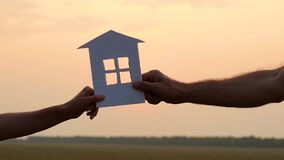 A man and a woman pass each other a model of a paper house on the background of the sunset. Concept of real estate stock video footage