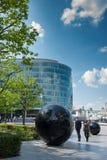 Man and woman pass sculptures on the Southbank. LONDON, UK - MAY 12, 2016: Man and woman pass spherical sculptures on the Southbank of the Thames royalty free stock photos