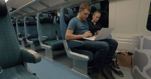 Commuters with laptop and cell in train stock footage