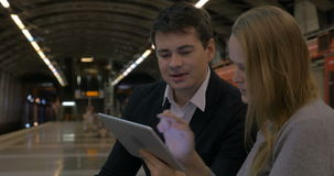Man and woman passing time with touch pad in the. Young people discussing some business issue using tablet computer while waiting at the metro station stock video footage