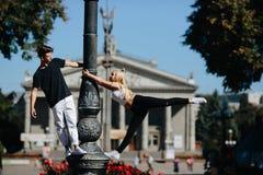 Man and woman performing acrobatic tricks. Man and women performing acrobatic tricks on the street Stock Image