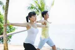 Man and Woman performing yoga. Royalty Free Stock Photos