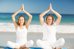 Man and woman performing yoga. Portrait of happy men and women performing yoga on beach Royalty Free Stock Images