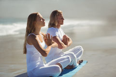 Man and woman performing yoga. Man and women performing yoga on beach Royalty Free Stock Images