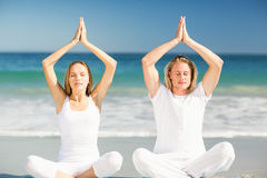 Man and woman performing yoga. Man and women performing yoga on beach Royalty Free Stock Image