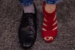 Person has a lady`s boot on one leg, and on the other a male boot. Man or woman? Person has woman´s red sandal and men´s black formal shoe.Gender conflict stock images