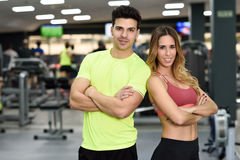 Man and woman personal trainers in the gym. Man and women personal trainers in the gym. Young girl and guy wearing sportswear with arms crossed royalty free stock photography