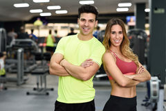 Man and woman personal trainers in the gym. Man and women personal trainers in the gym. Young girl and guy wearing sportswear with arms crossed stock images