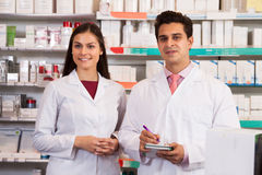 Man and woman pharmacists at the chemists shop. Smiling men and women pharmacists at the chemists shop stock image