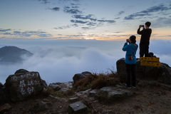 Man and woman photographing at the Lantau Peak at dawn Royalty Free Stock Images