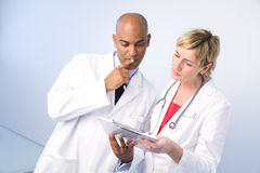 Man and woman physicians. A man and woman doctor looking at a chart wearing white coats and stethoscope Royalty Free Stock Photo