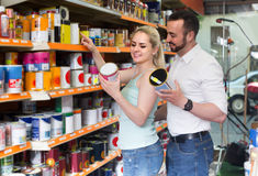 Man and woman picking paint tin together in household shop Stock Images