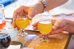 Man and Woman Picking Up Small Glass of Micro Brew Beer at Bar. Man and Woman Picking Up Small Glasses of Micro Brew Beers at Bar stock photos