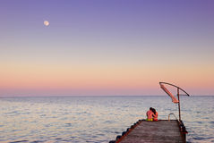 Man and woman on a pier in the moonlight Stock Images