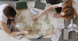 Man and woman are planning vacation using a world map and other travel accessories.
