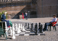 Man and woman play a chess near a castel Sant'Angelo Royalty Free Stock Photography