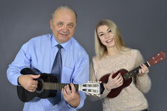 Man and woman play the guitar. Man and women play the guitar and laughing Royalty Free Stock Photography