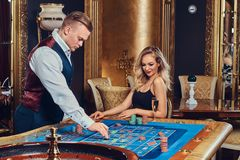 A man and woman play roulette. Royalty Free Stock Photos