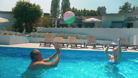 Man and Woman Playing Ball in Home Pool stock video footage