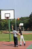 Man and Woman Playing Basketball - Vertical Stock Photo