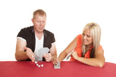 Man and woman playing cards he rolls dice Royalty Free Stock Image