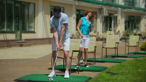 Man and woman playing golf near a clubhouse stock video