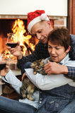 Man and woman playing with a kitten by the fireplace Royalty Free Stock Photos