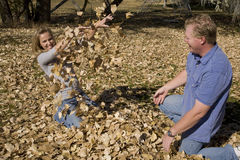 Man and woman playing in leaves Royalty Free Stock Photography