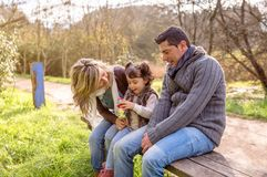 Man and woman playing with little girl sitting on Stock Photos
