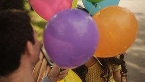 Man and woman playing in the park with balloons stock video footage