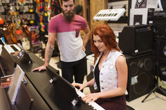 Man and woman playing piano at music store Stock Photography