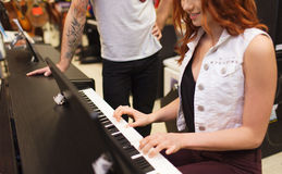 Man and woman playing piano at music store Royalty Free Stock Photography