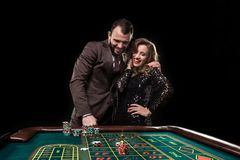 Man and woman playing at roulette table in casino stock photo