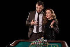 Man and woman playing at roulette table in casino royalty free stock image