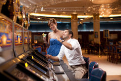 Man and woman playing he slot machine Royalty Free Stock Image