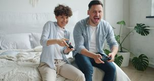 Man and woman playing video game sitting on bed in apartment having fun. Man and woman beautiful couple are playing video game sitting on bed in apartment having stock footage