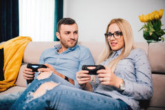 Man and woman playing video games. man is angry and girl is winning. Details of modern lifestyle and free time concept. Man and blonde women playing video games Royalty Free Stock Photos