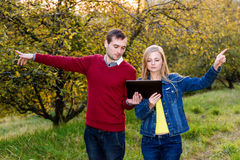 man and woman pointing in opposite directions Stock Image