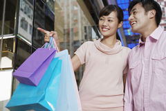 Man With Woman Pointing At Window Display. Happy young men with women carrying shopping bags while pointing at window display Stock Photography