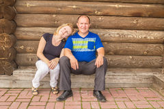 Man and woman. Portrait of young people in the background log wall royalty free stock images