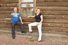 Man and woman. Portrait of young people in the background log wall stock image