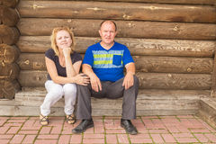Man and woman. Portrait of young people in the background log wall royalty free stock image