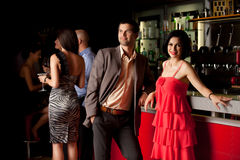 Man and woman posing beside bar Stock Photography