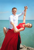 Man and woman posing in dance by the sea. Stock Photography