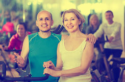 Man and woman posing in a gym and smiling. Smiling mature men and women posing in a gym and smiling stock image