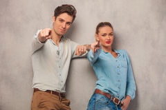 Man and woman posing in studio pointing fingers while leaning Stock Images
