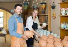 Man and woman potters holding ceramic vessels in atelier Stock Photos