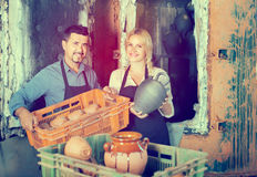 Man and woman potters holding ceramic vessels in atelier Royalty Free Stock Photography