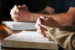 Man & Woman Praying Bibles. A man and woman pray together with their hands resting upon Holy Bibles (Christian Image, shallow focus point on woman's foreground stock photos